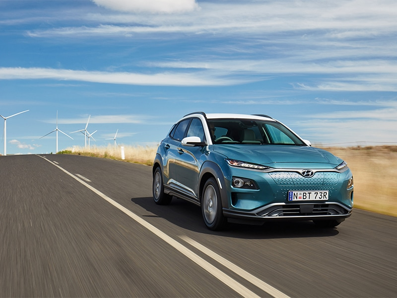 Hyundai Kona Electric driving down road with windmills in background