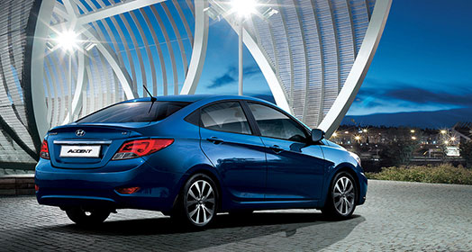 Side-rear view of blue Accent parked in front of the arch shaped architecture in the evening