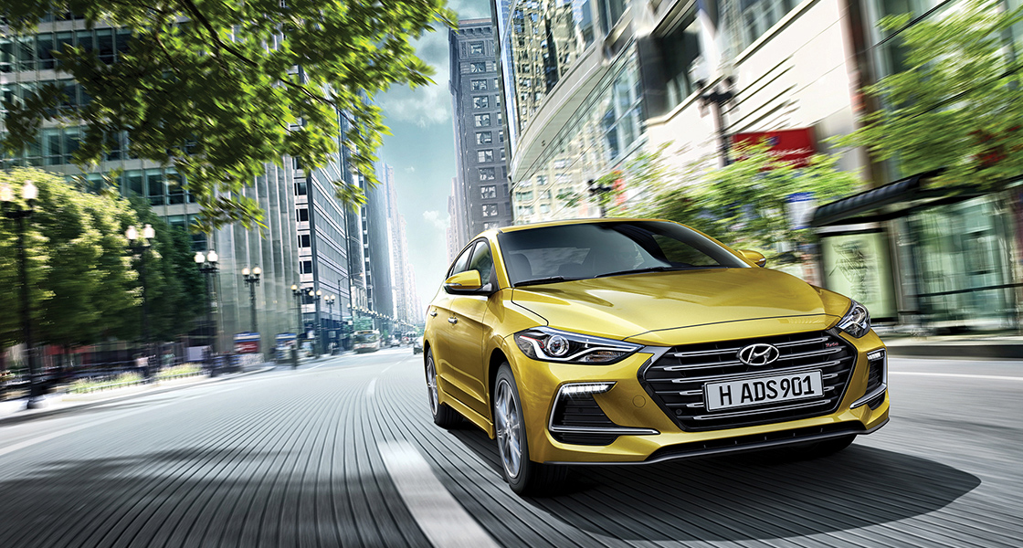 Right side front view of yellow Elantra Sport driving on the street