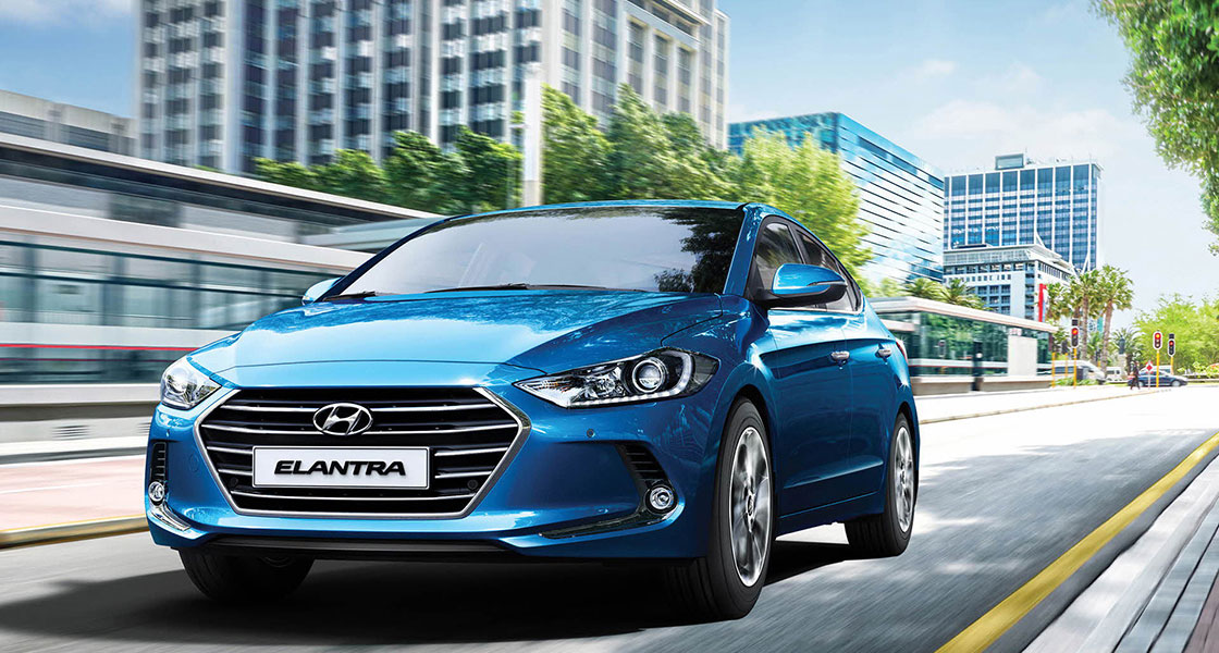 Front view of driving blue Elantra on the road in the city