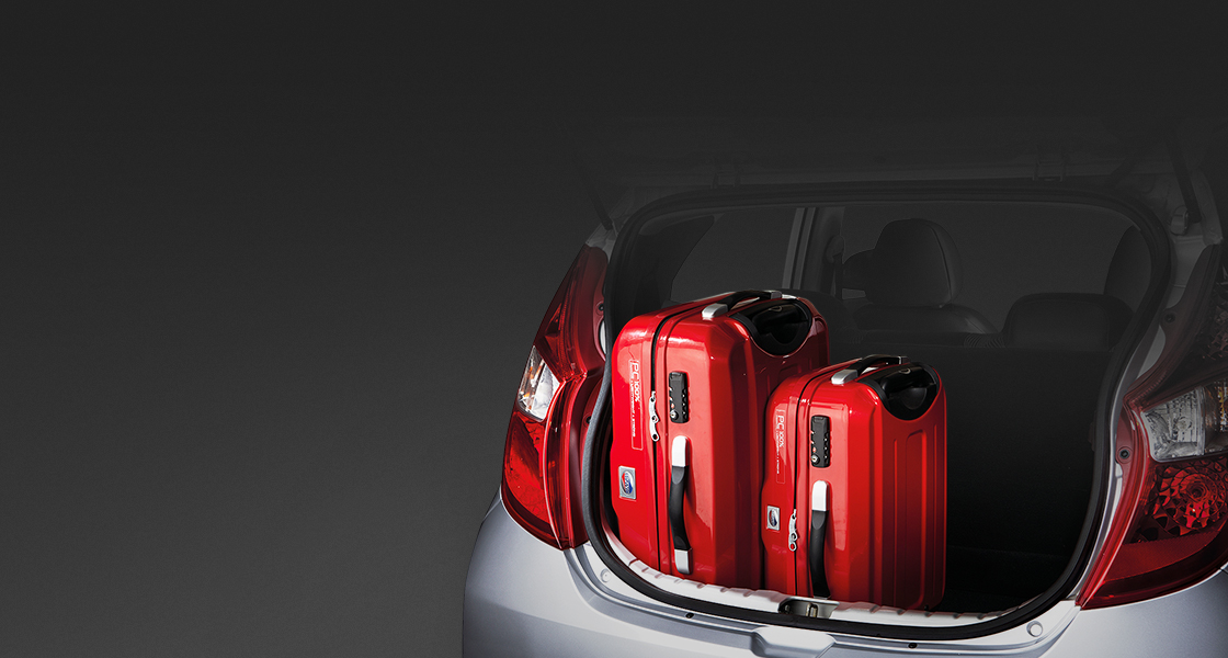 Two red luggage loaded in trunk