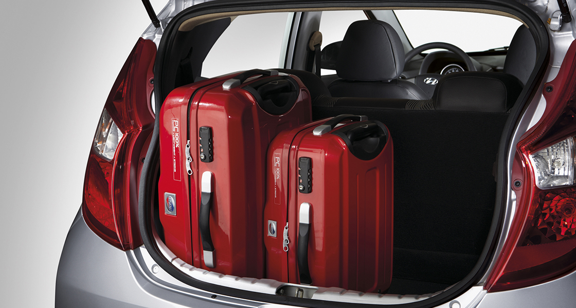 Two red luggage loaded on the trunk