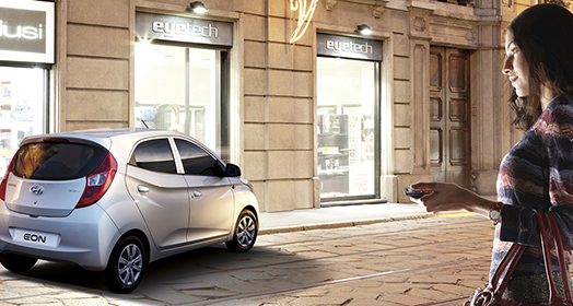 A woman approaching to silver Eon parked in front of the building