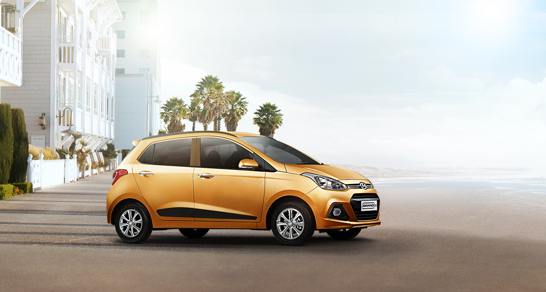 Side view of tangerine orange Grand i10 on a clear day