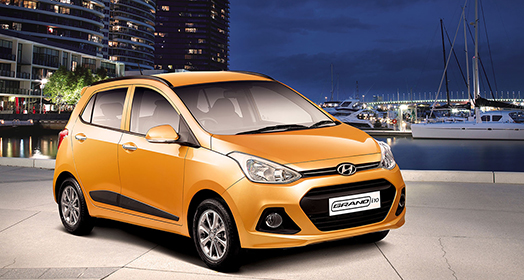 Side-front view of orange Grandi10 with lakeside view at night
