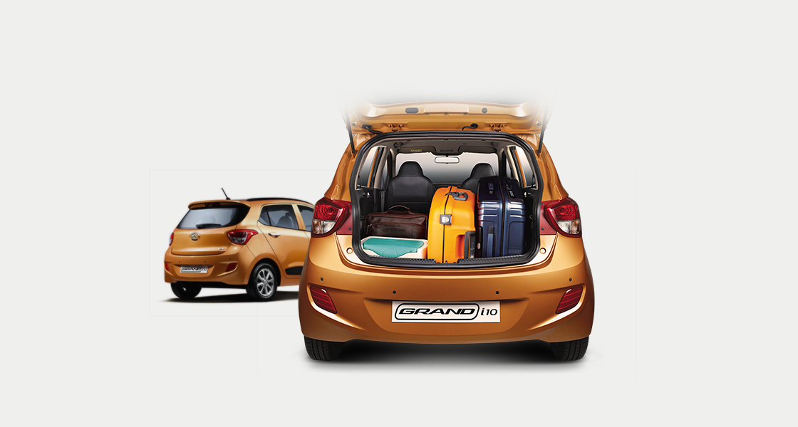 Two rear view of tangerine orange Grand i10 with many luggage loaded on the trunk