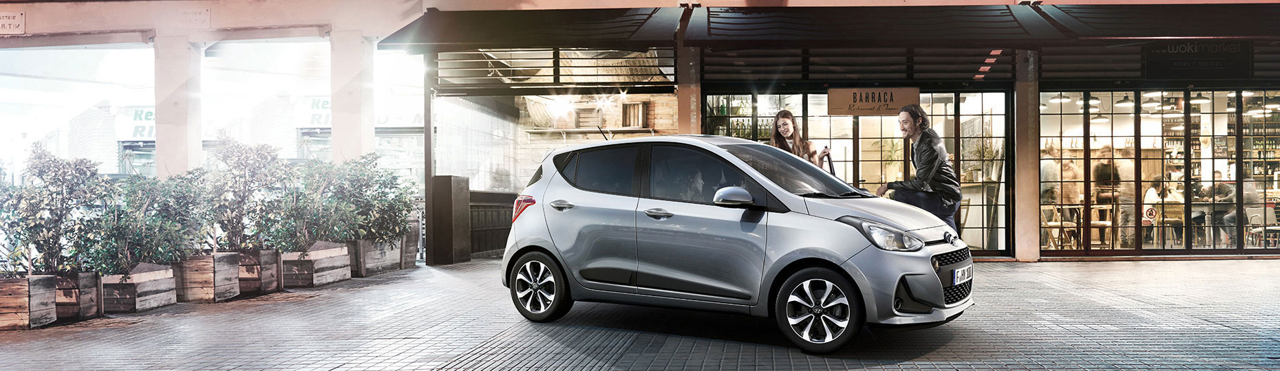 Silver i10 is parked in front of a café