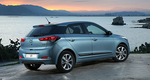 Right side rear view of skyblue i20 parked on the road with the river beside