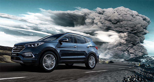 Side view of navy Santa Fe driving on the road with dark smoke behind in the sky