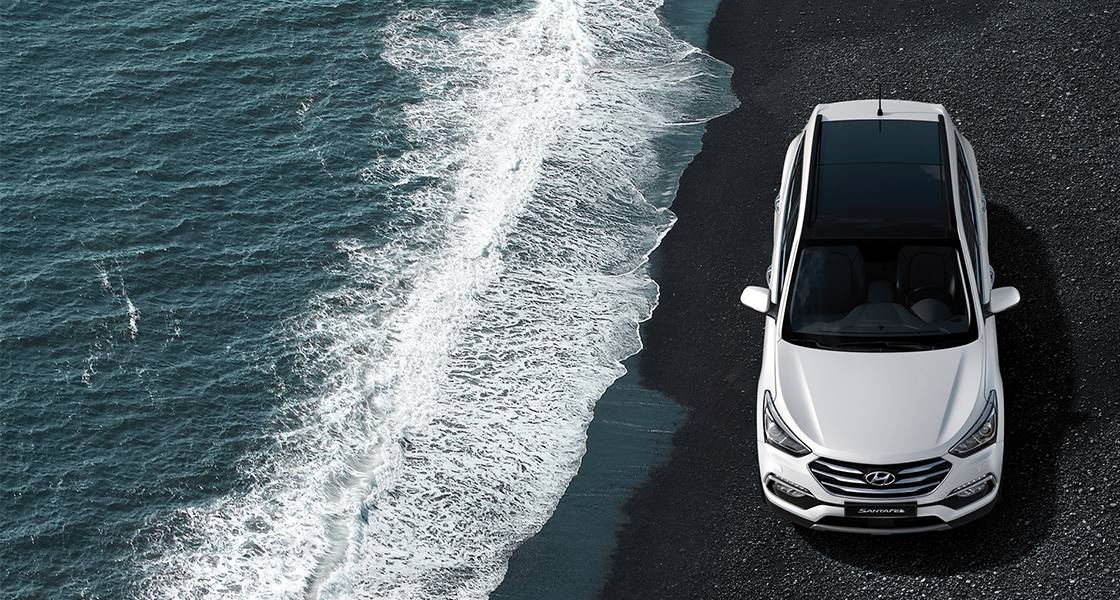 Sky view of white Santa Fe driving on the seashore
