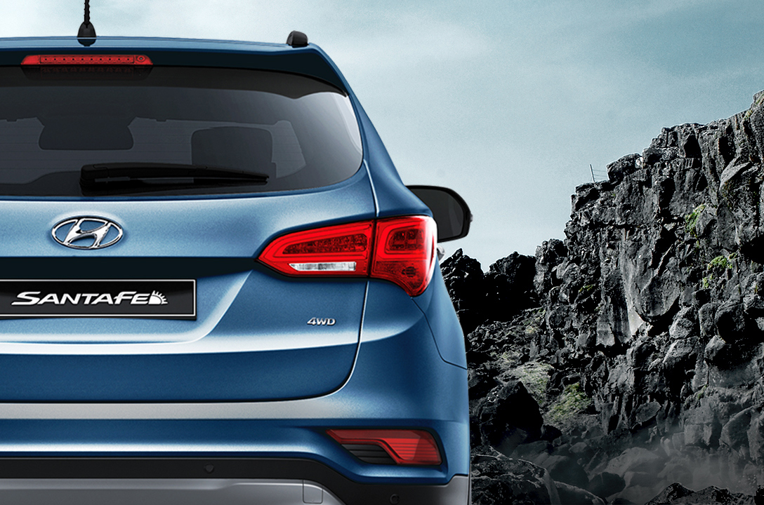 Rear view of blue Santa Fe with mountain background