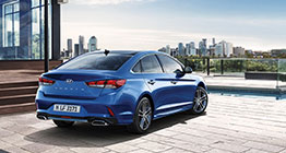 Right side rear view of blue sonata in front of house