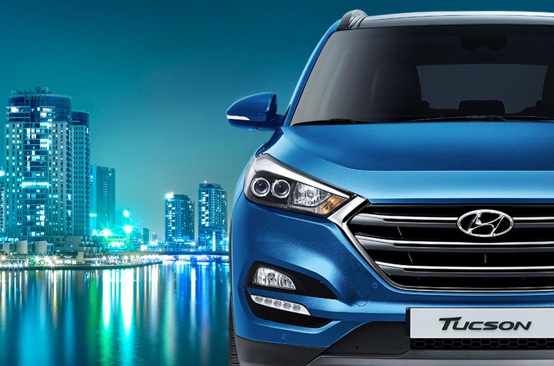 Front view of blue Tucson with night city view