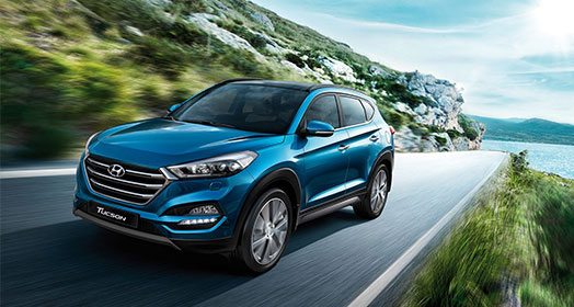 Left side front view of light blue Tucson driving on the mountainous road