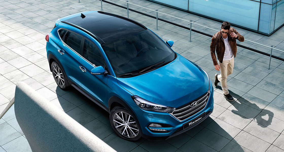Sky view of a man standing next to blue Tucson