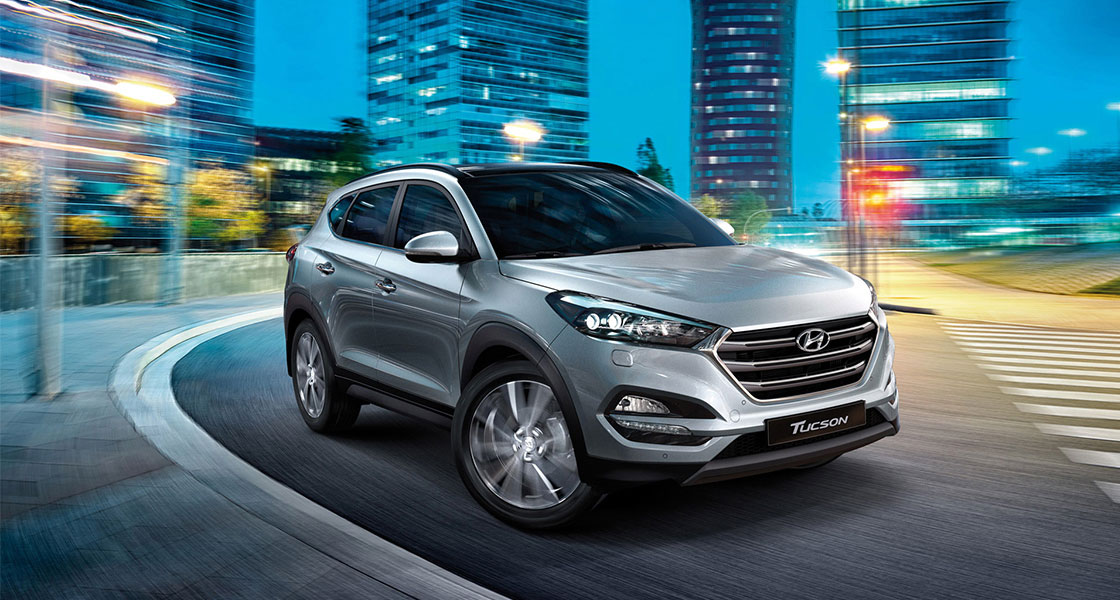 Right side front view of silver Tucson on the road in the city at a night