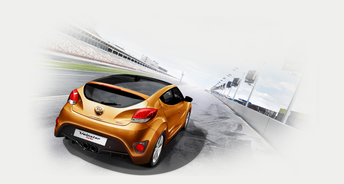 Rear view of tangerine car of driving Veloster Turbo