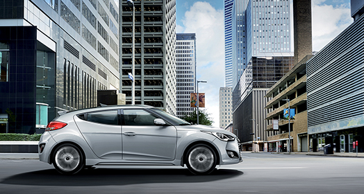 Side view of silver Veloster Turbo driving in the city
