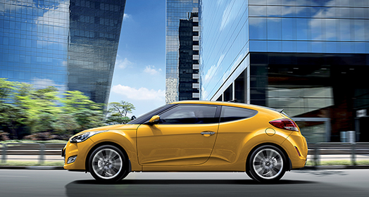 Left side view of yellow Veloster behind buildings