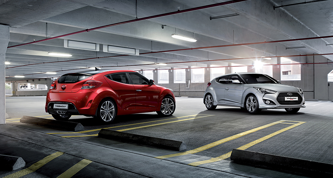One side rear view of red veloster and side view of gray veloster parked in indoor parking lot