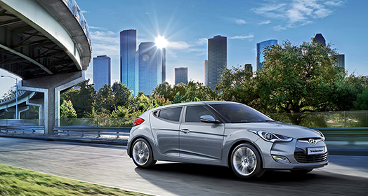 Side view of silver Veloster driving with the city background