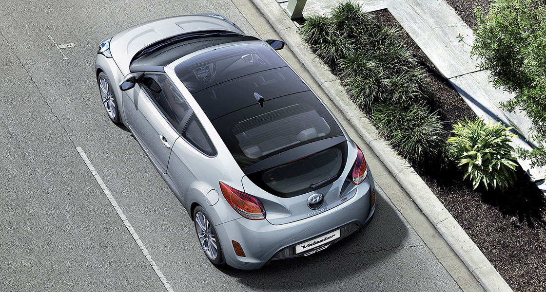 Sky view of silver Veloster from left side rear viewpoint