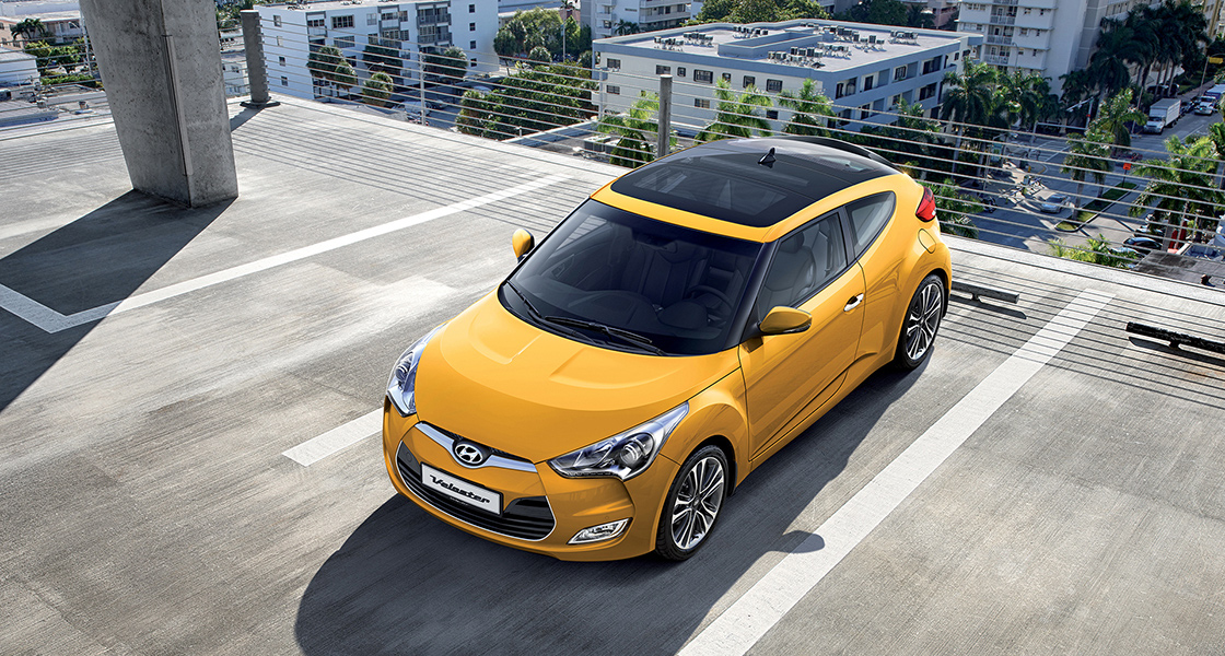 Sky view of yellow veloster parked on the roof of the building