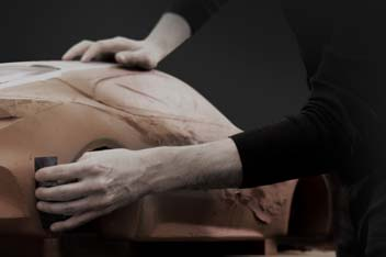 Closer view of hands polishing a clay model.