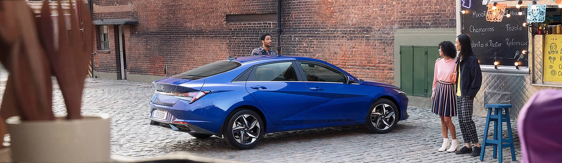 Blue Elantra is placed in front of a building with white color
