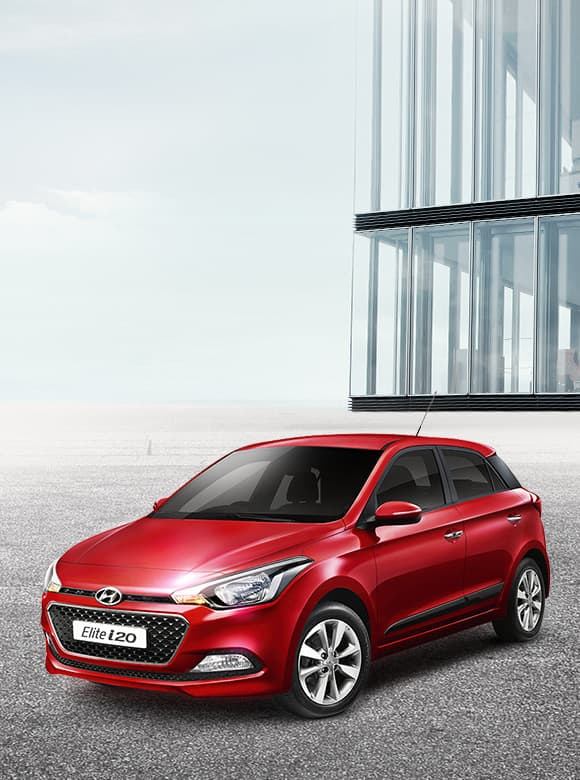 Red color Elite i20 is placed in front of a modern building