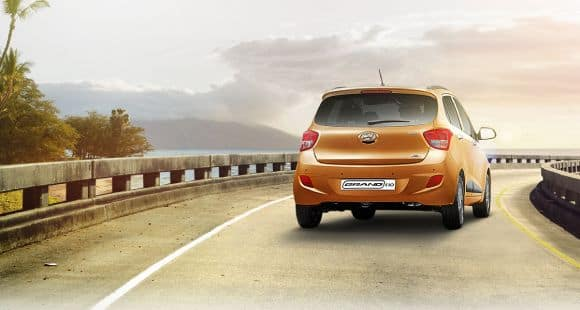 Rear view of tangerine orange Grand i10 driving with sunset background