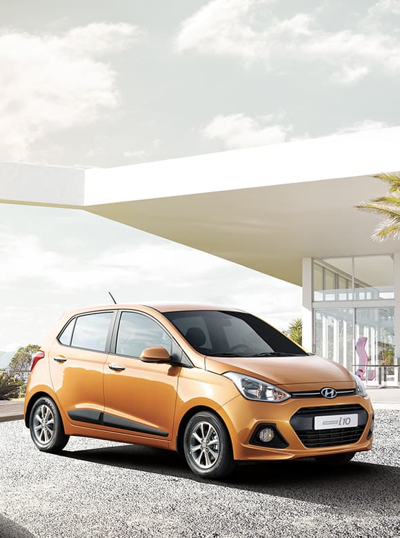 Yellow color Grand i10 is placed in front of a modern building