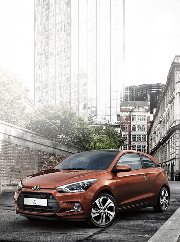 Side front view of orange i20 Coupe driving on the road