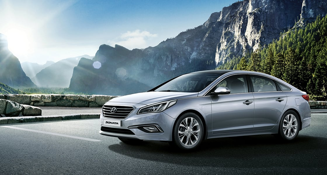 Side view of gray Sonata with mountain view behind