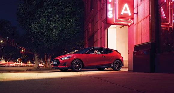 Left side view of red veloster parking