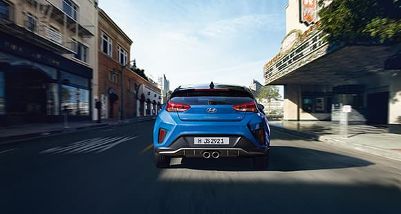 Rear view of blue veloster driving on the road