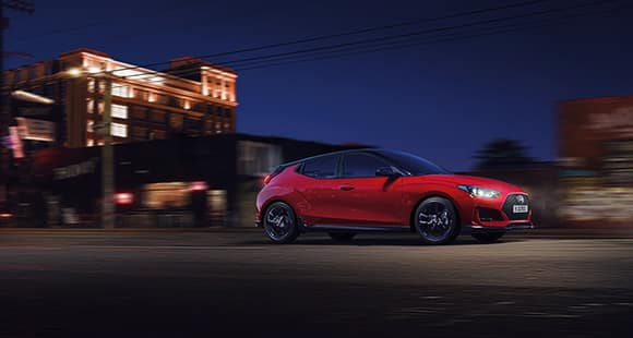 Right side view of red veloster driving on the road