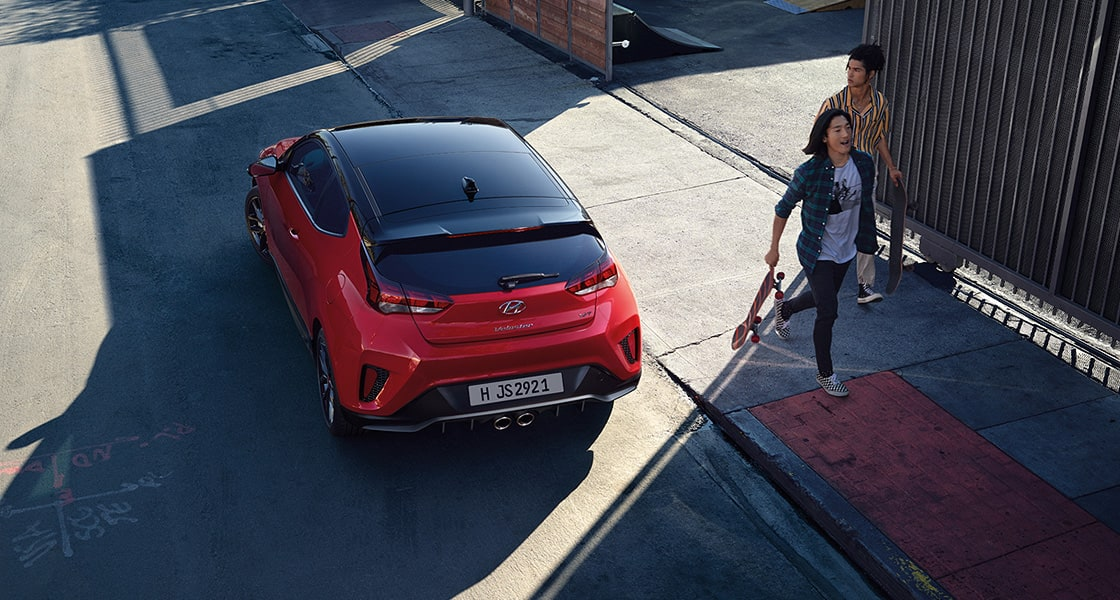 Red Veloster parked on the road beside persons.