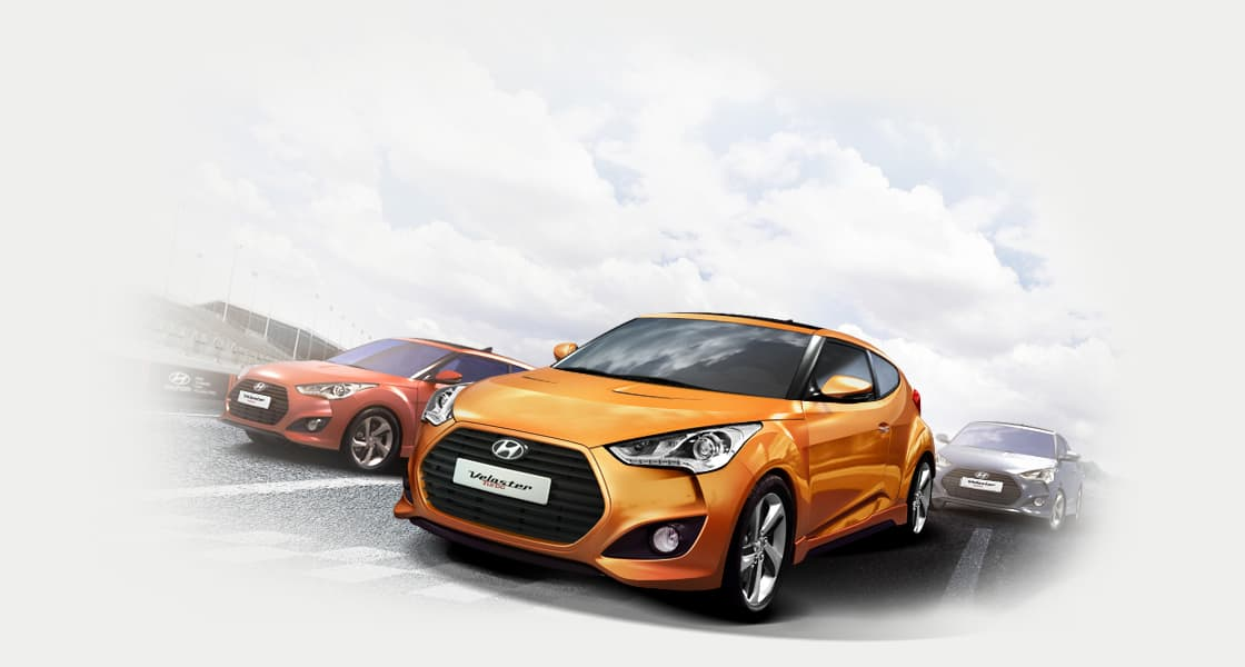 Side front view of three Veloster Turbo cars driving on the road
