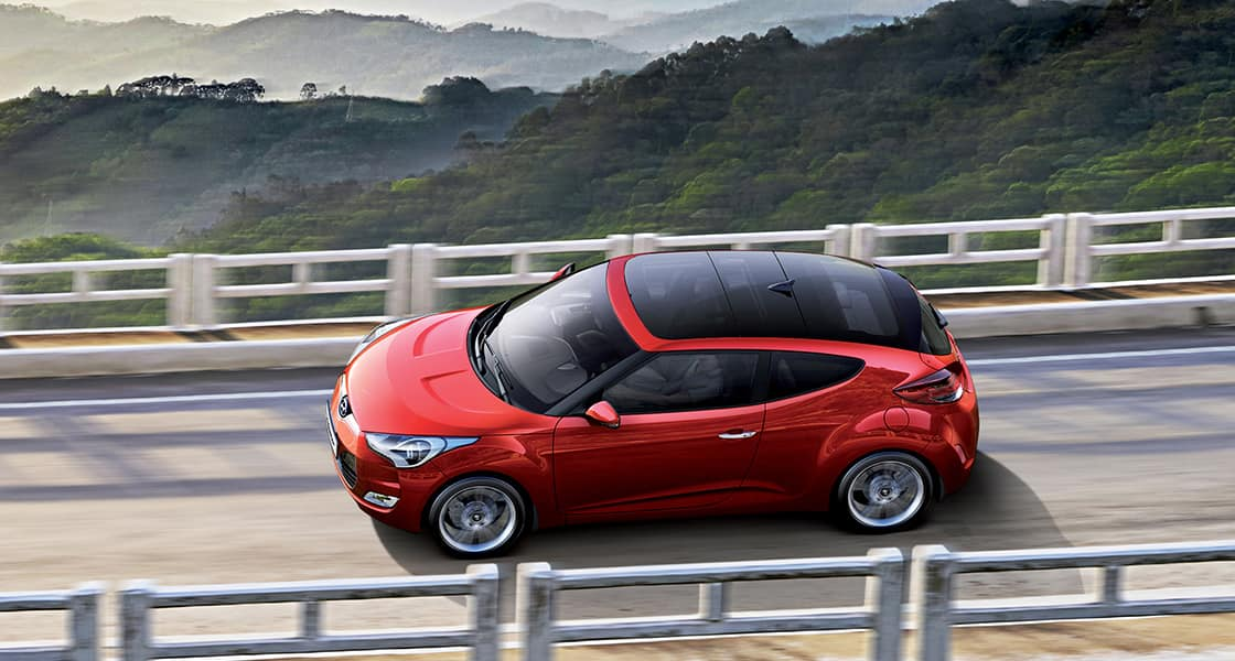 Sky view of driving red Veloster from left side viewpoint