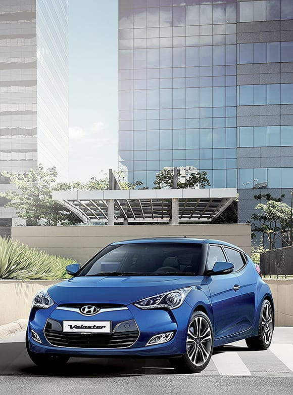 Blue color Veloster is placed in front of a modern building
