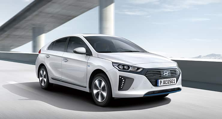 Side front view of white Ioniq plug-in hybrid driving on the highway