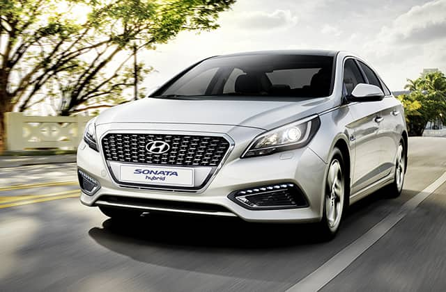Front view of silver Sonata Hybrid driving on the road
