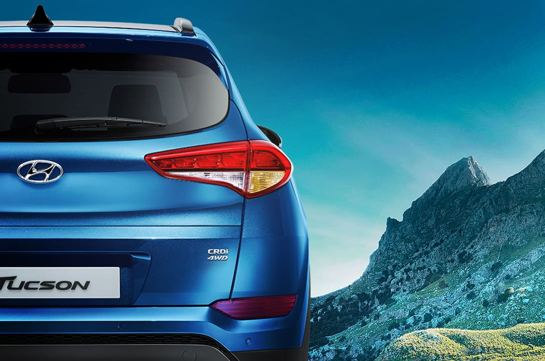 Rear view of blue Tucson with mountain background
