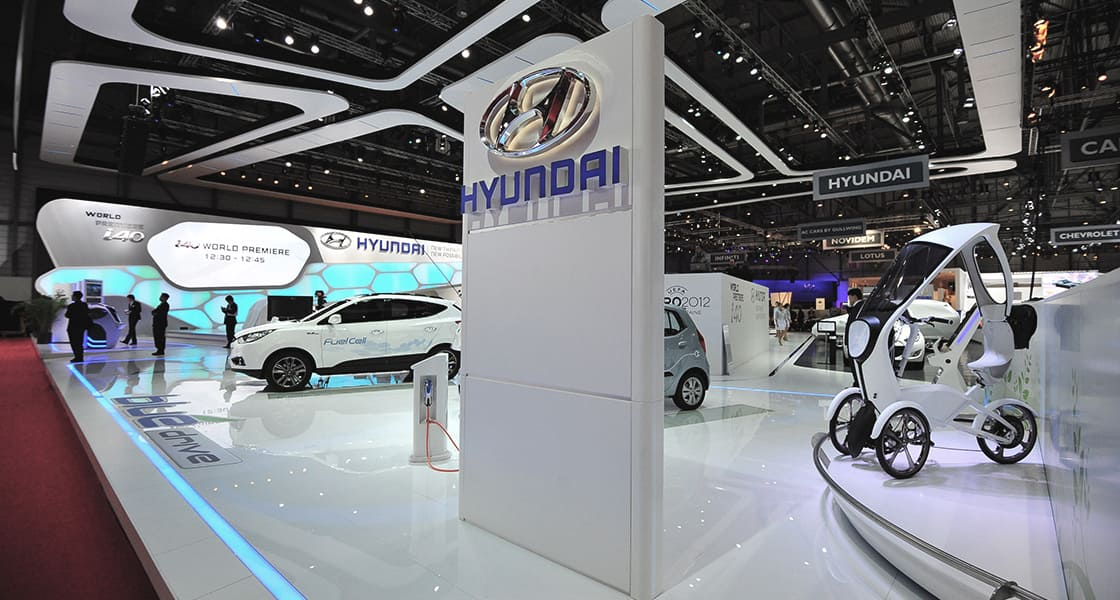 A white SUV equipped with fuel cell, a charger, a tricycle and a huge structure with embossed logo of hyundai are at the hyundai motors venue at 2011 Geneva International Motorshow