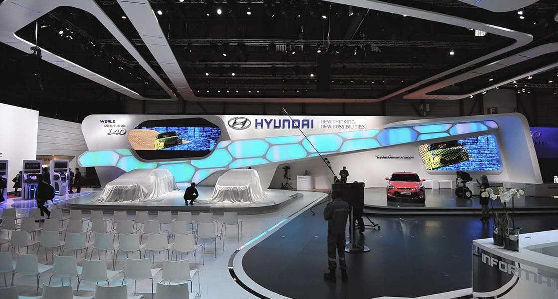 There are 2 veiled car on the show stage and empty chairs in rows at the hyundai motors venue at 2011 Geneva International Motorshow