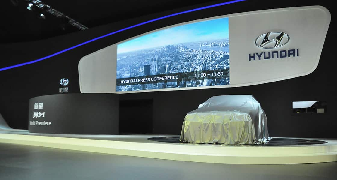 There are a secret car covered by a cloth on the hyundai's show stage and a huge electronic bulletin board behind notifying the time of press conference at 2011 Guangzhou International Motorshow