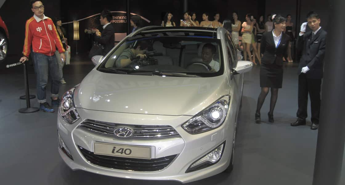 There are 2 men recording a video inside a gray i40 displayed and people are standing around the car including female models at 2011 Guangzhou International Motorshow