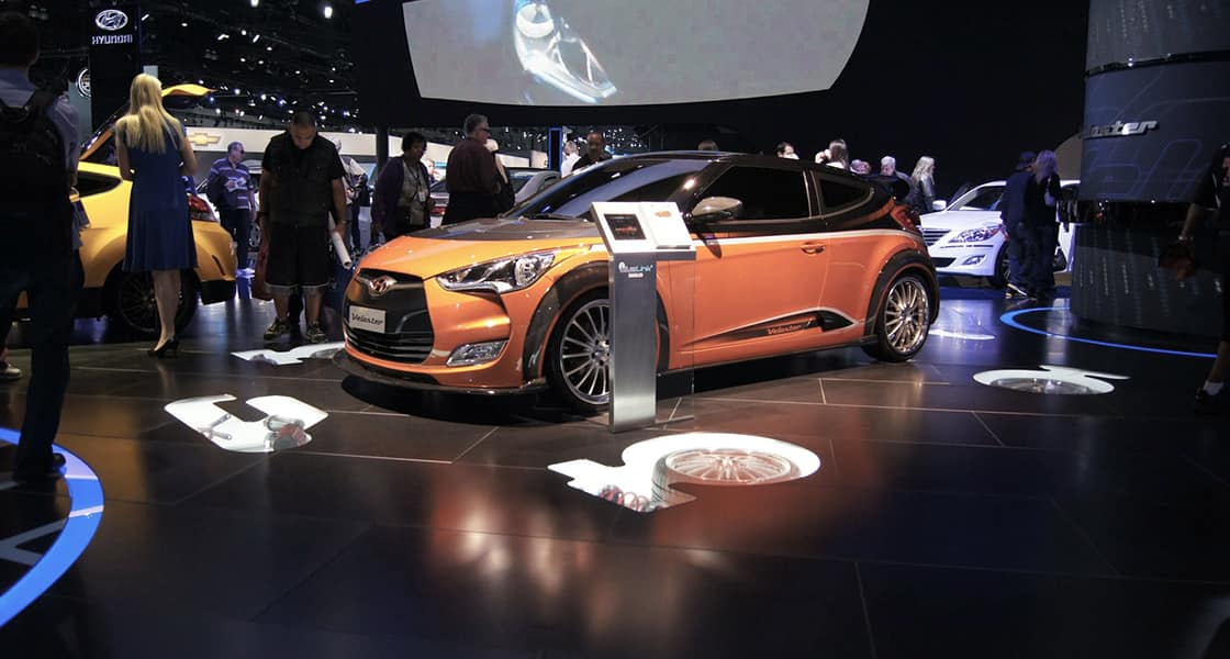 The orange veloster with a pamphlet around visitors on the show stage at 2011 Los Angeles International Motorshow