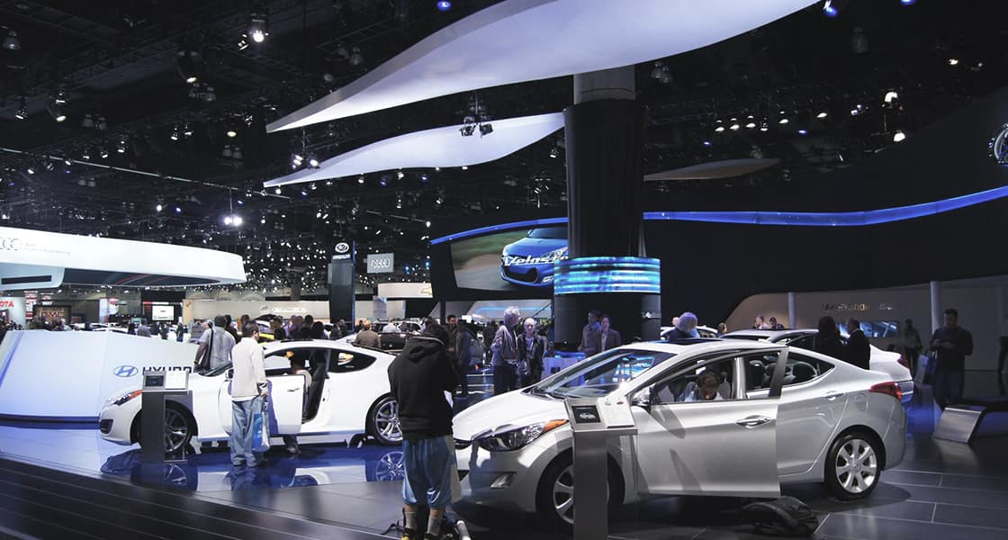 Many visitors are browsing and getting on the displayed cars at 2011 Los Angeles International Motorshow